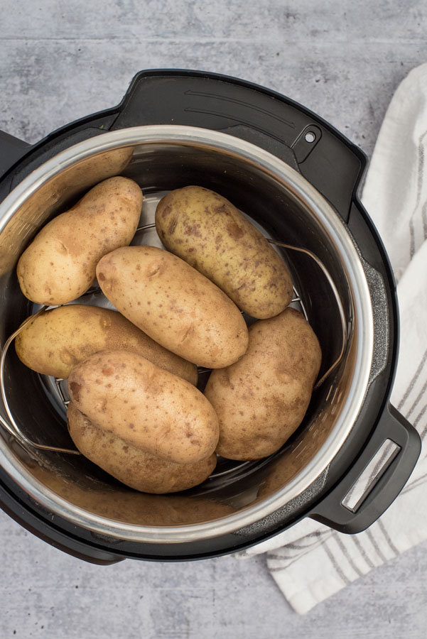 instant pot with several large baking potatoes inside