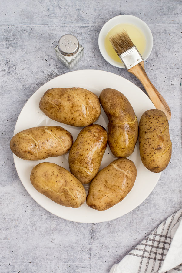 white plate of large baking potatoes brushed with olive oil for roasting or crisping in a pressure cookier