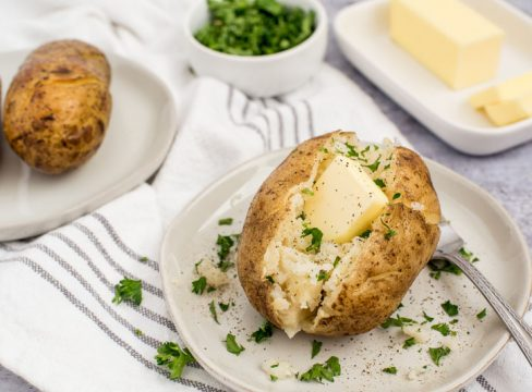 Instant pot baked potatoes with a pat of butter and fresh herbs sprinkled on top on a white plate with a butter dish in the background