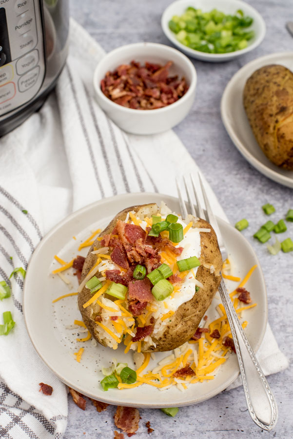 instant pot baked potatoes topped with scallions, shredded cheese and crumbled bacon on a white plate