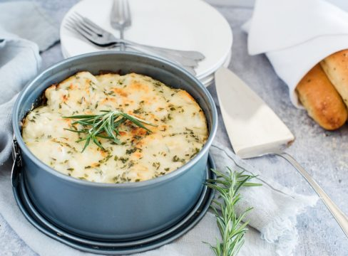 freshly made Instant pot white chicken alfredo lasagna in a round springform pan with a sprig of rosemary and breadsticks