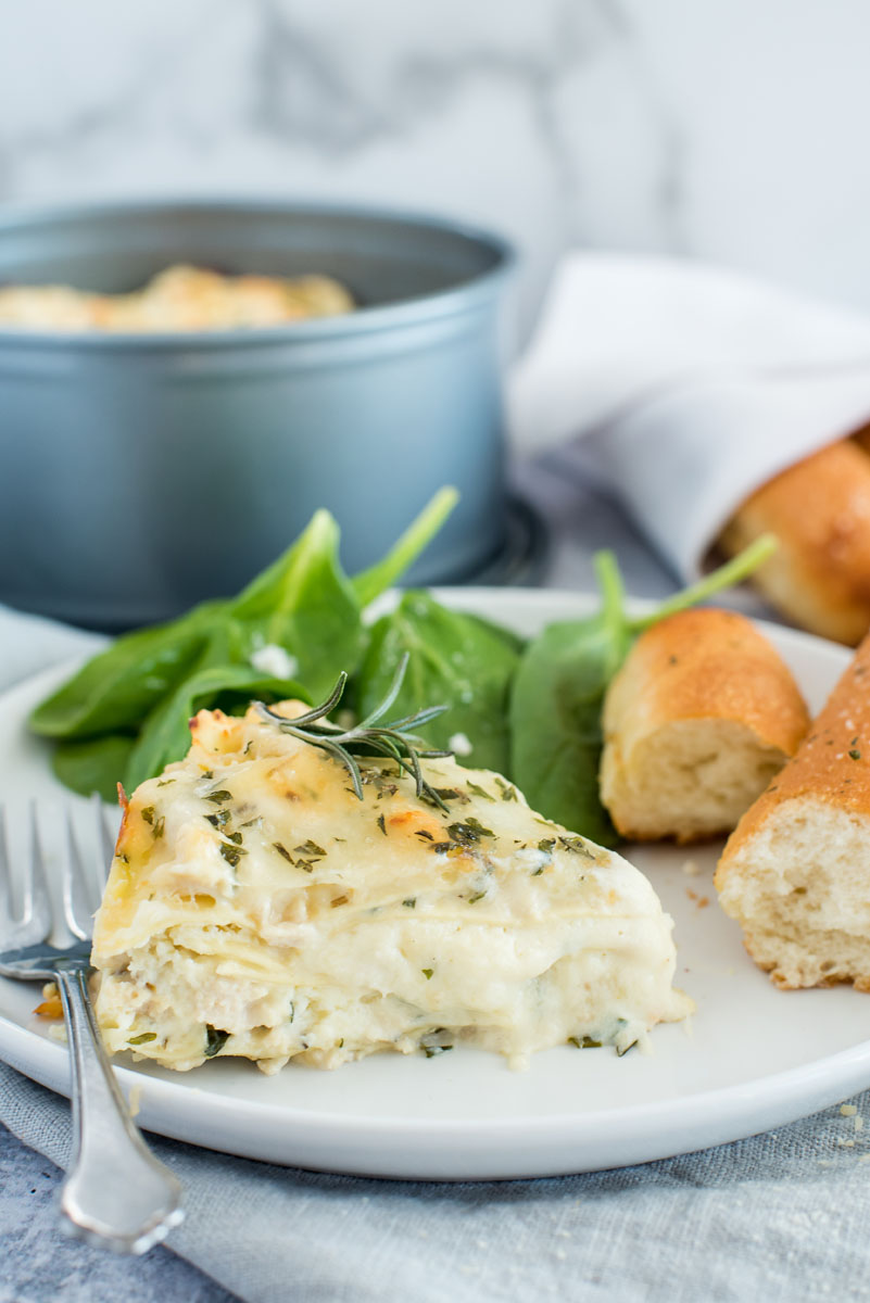 Instant pot white chicken lasagna on a white plate with a bread stick and greens