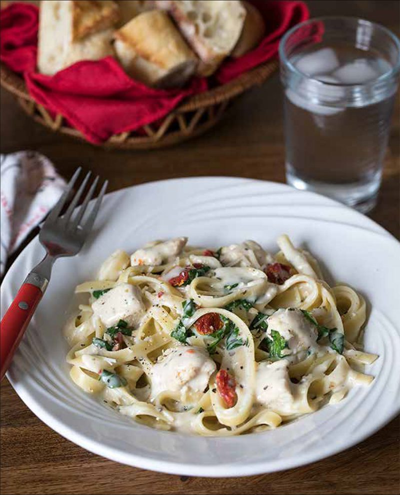 Tuscan Garlic Chicken from the Electric Pressure Cooker Cookbook - featuring 45 degree shot of fettuccini noodles with a white garlic cream sauce, parsley, sundried tomatoes, and chicken, with a red fork on the side