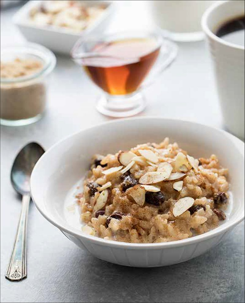 Maple Almond Risotto from the Electric Pressure Cooker Cookbook - featuring 45 degree shot of a white bowl filled with a tan risotto, a splash of milk, raisins, and sliced almonds with a dash of cinnamon on top