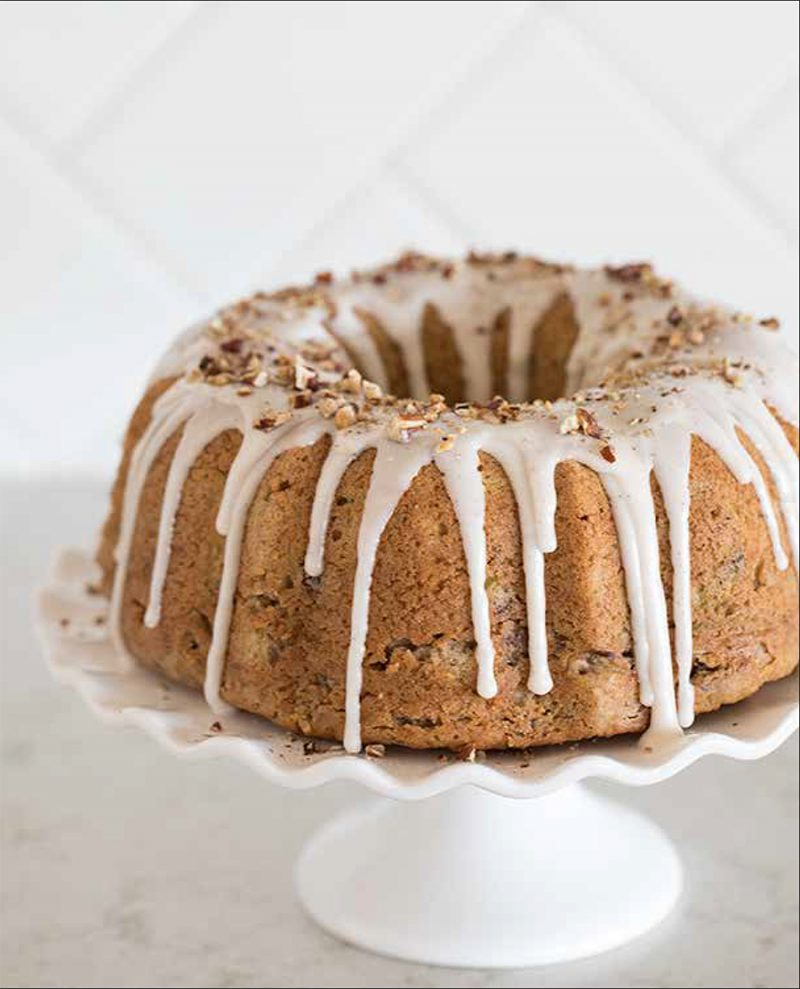 Cinnamon Zucchini Bread from the Electric Pressure Cooker Cookbook - featuring a head-on shot of zucchini bread made in a bundt pan with white cinnamon icing drizzled in drips down the sides and crushed nuts sprinkled around the top