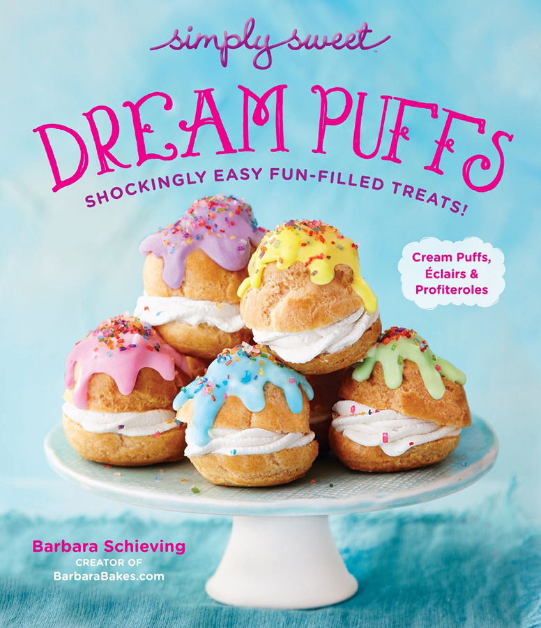 Front cover of Dream Puffs cookbook by Barbara Schieving, featuring a light blue background with a white cake stand loaded up with several cream puffs that have been topped with pastel rainbow colored glaze and rainbow sprinkles