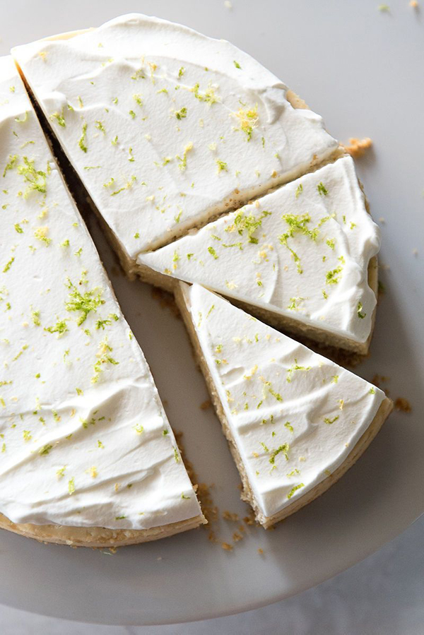 overhead shot of Instant Pot Key Lime Pie from Mountain Mama Cooks' review of Instantly Sweet - featuring a white plate with a creamy off-white cheeseake topped with white whipped cream and garnished with lime zest