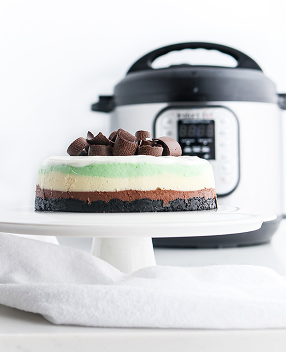 straight-on shot included in the Instantly Sweet Dessert Cookbook - featuring a white cake stand topped with triple layer mint cheesecake with chocolate curls and an Instant Pot in the background