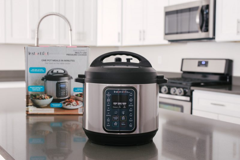 direct front shot of the Instant Pot Duo Gourmet on a gray countertop with the box and white cabinets in the background