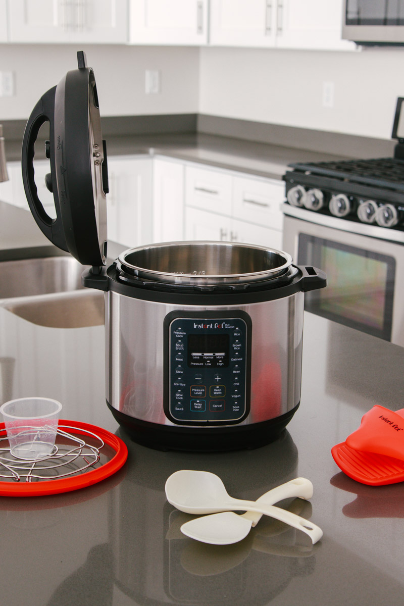 45 degree shot of the Instant Pot Duo Gourmet with the lid resting upright in the lid fin slot, surrounded by the accessories that come with it on a gray countertop