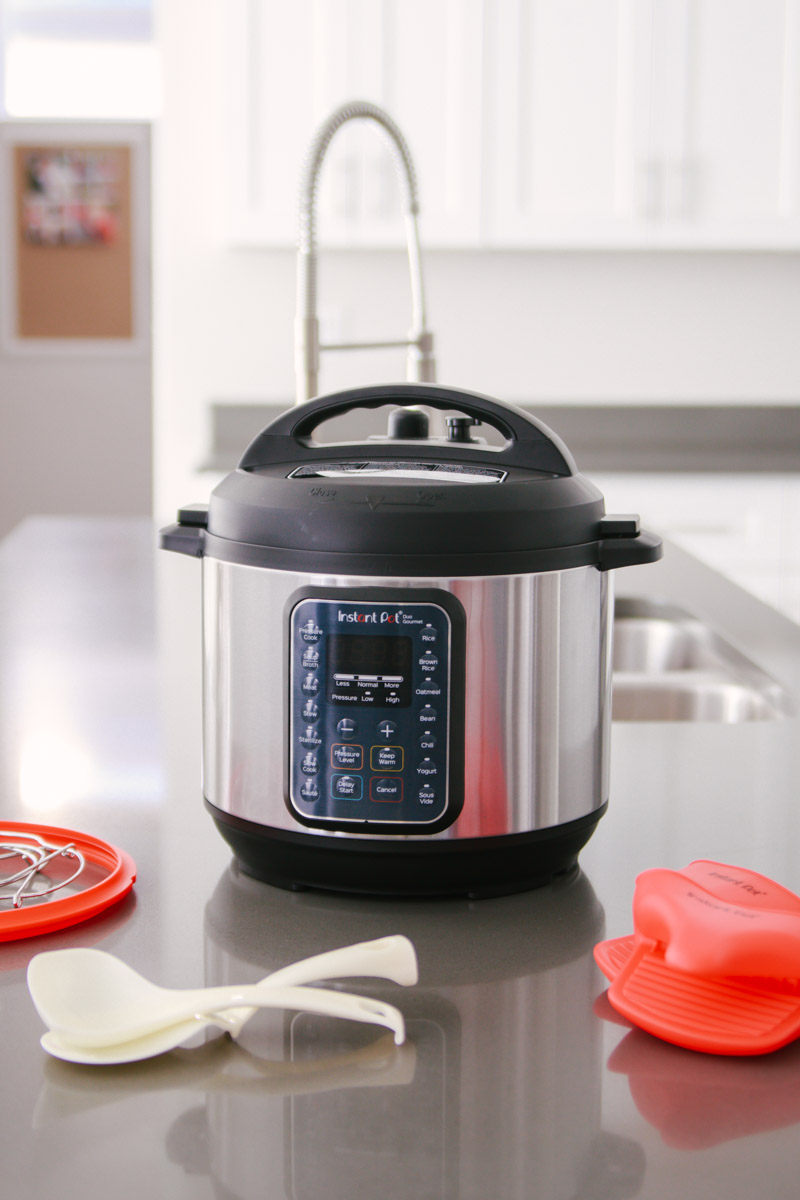 front shot of the Instant Pot Duo Gourmet with the lid in place with the accessories on the counter in front