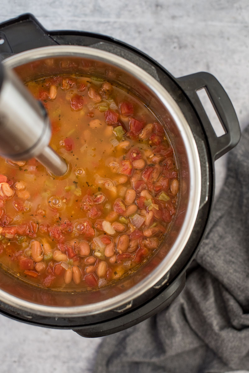 overhead shot of Instant Pot Pinto Bean Soup, with an immersion blender blending someo fo the beans, bacon, and tomatoes in the broth