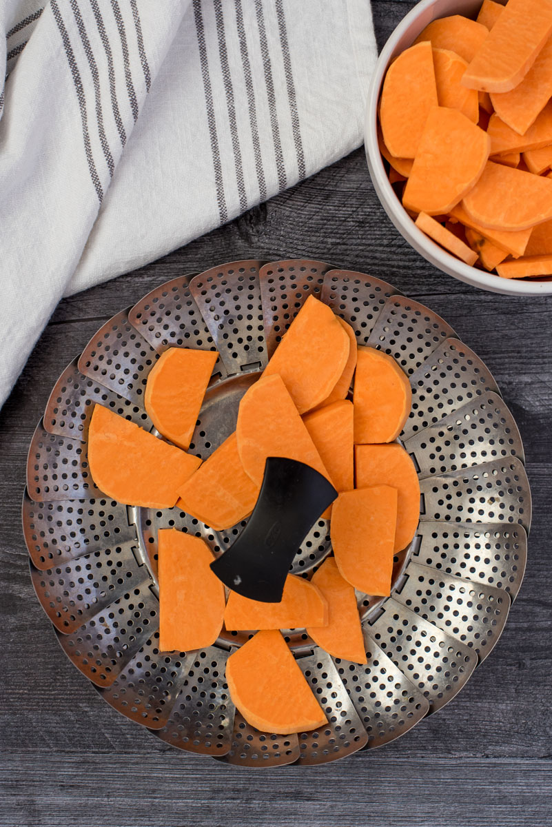sweet potato slices on a metal steamer basket