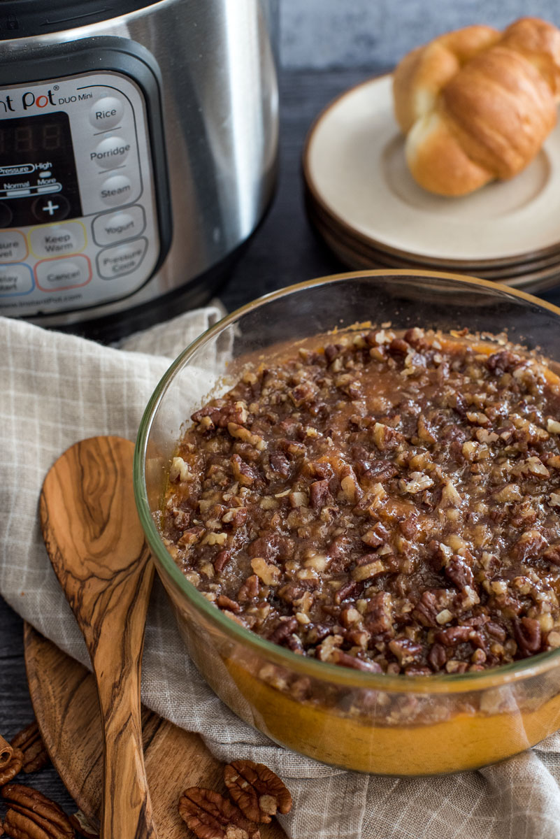 sweet potat casserole in front of an instant pot with a sooden spoon and a nutty crust