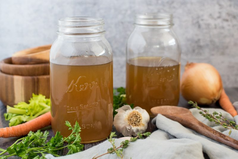 Side view of mason jars filled with Instant Pot turkey stock surrounded by fresh garlic, onion, thyme, parsley, and carrots.