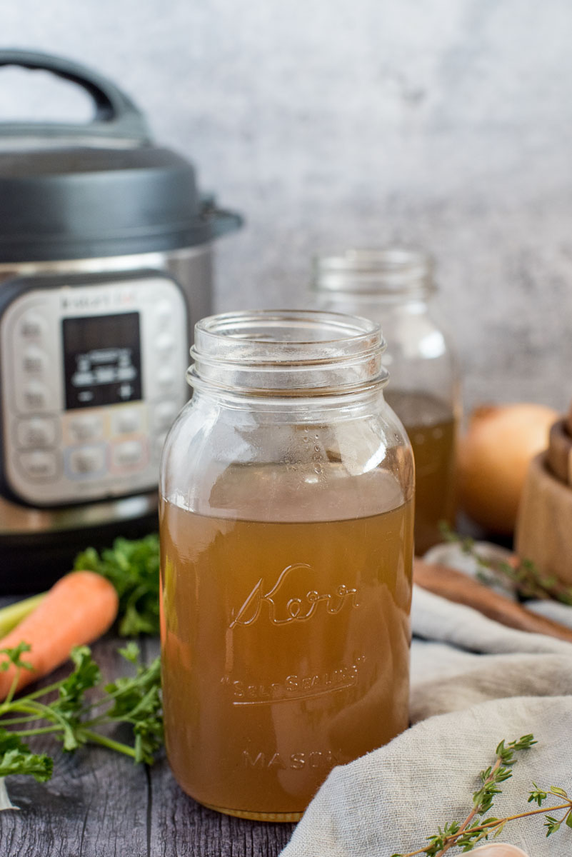 Insta Pot turkey stock in a mason jar in front of an Instant Pot, surrounded by fresh thyme, parsley, and carrots.