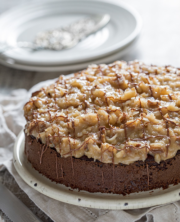 45 degree shot included in the Instantly Sweet Dessert Cookbook - featuring a white plate topped with german chocolate cake with coconut almond frosting and a crisscross chocolate drizzle