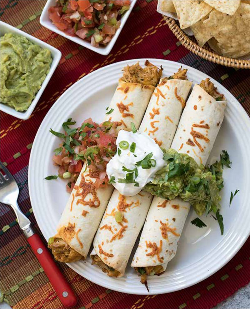 Baked Chicken Taquitos from the Electric Pressure Cooker Cookbook - featuring overhead shot of a white plate with three taquitos on top, garnished with tomato salas, guacamole, sour cream, cilantro and green onions