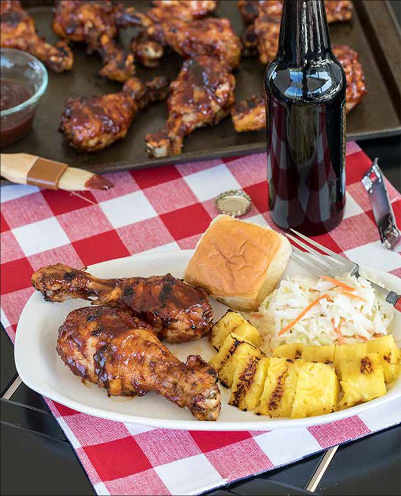 Quick Chicken Legs from the Electric Pressure Cooker Cookbook - featuring 45 degree shot of a white plate with two BBQ chicken legs, grilled pineapple, coleslaw, a roll, with a bottle of rootbeer and a dark sheet pan full of additional chicken legs in the background