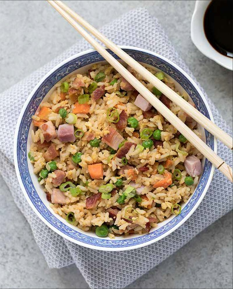 Ham Fried Rice from the Electric Pressure Cooker Cookbook - featuring overhead shot of yellow fried rice with bacon, carrots, ham, peas, fried egg, and green onions, with chopsticks balanced on top of the bowl and a small white bowl of soy sauce in the background