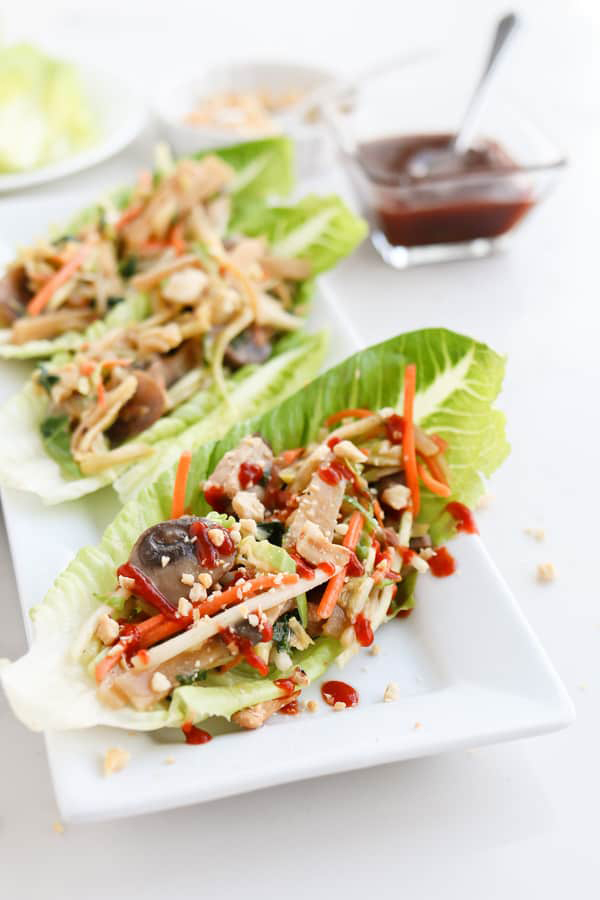 45 degree shot of Instant Pot Moo Shu Pork from Tidbits' review of the Electric Pressure Cooker Cookbook - featuring a white platter with three long lettuce leaves filled with moo shoo pork and garnished with matchstick carrots and red sauce