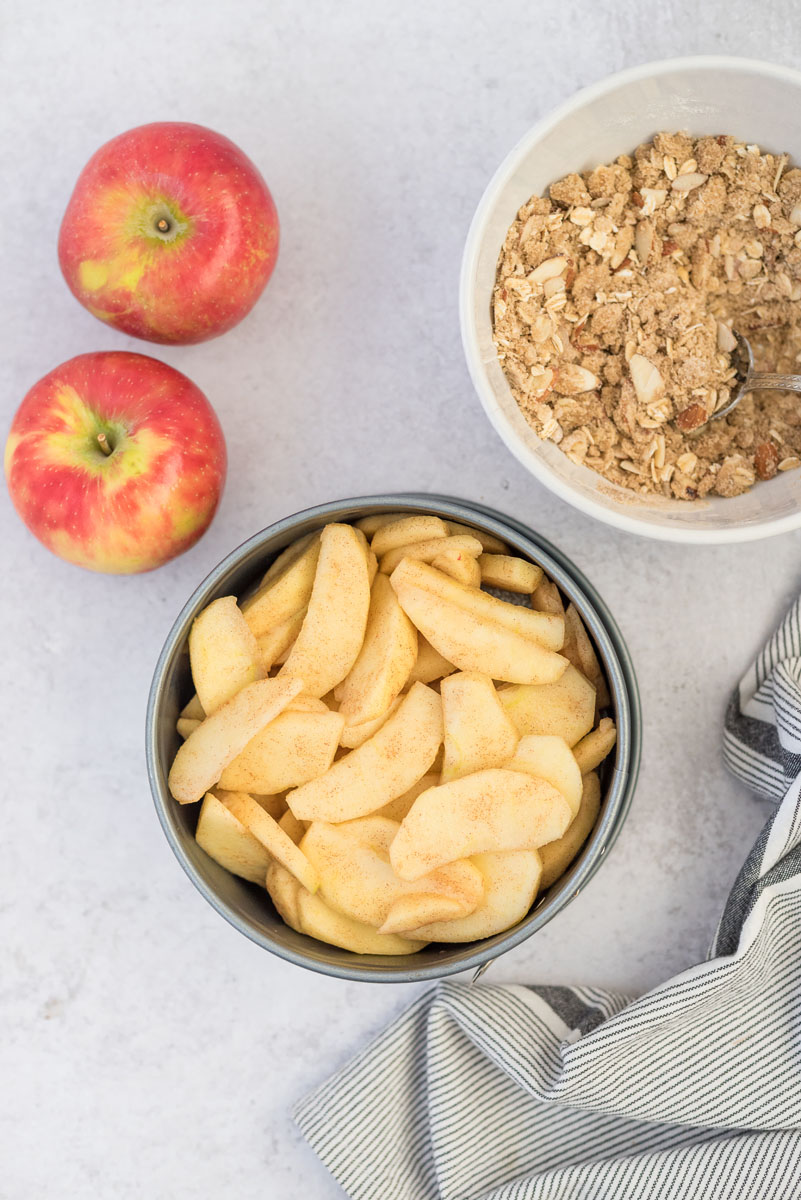 an overhead shot of diced apples in the springform pan with two red apples on the upper left a bowl full of the crumble topping on the right
