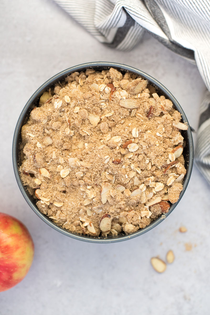 an overhead shot of the Instant Pot apple crisp topped and ready to go in the INstant Pot with a red apple and a white striped napkin in the background