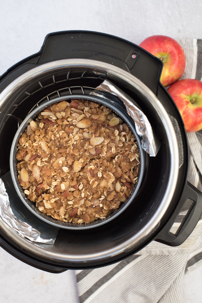 an overhead shot of the instide of the Instant Pot with a foil sling and a springform pan containing finished Instant Pot apple crisp with two red apples in the upper right