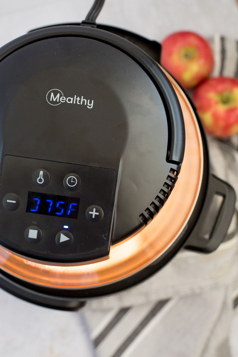 an overhead shot of the Mealthy CrispLid air fryer lid on and running, with apples in the background