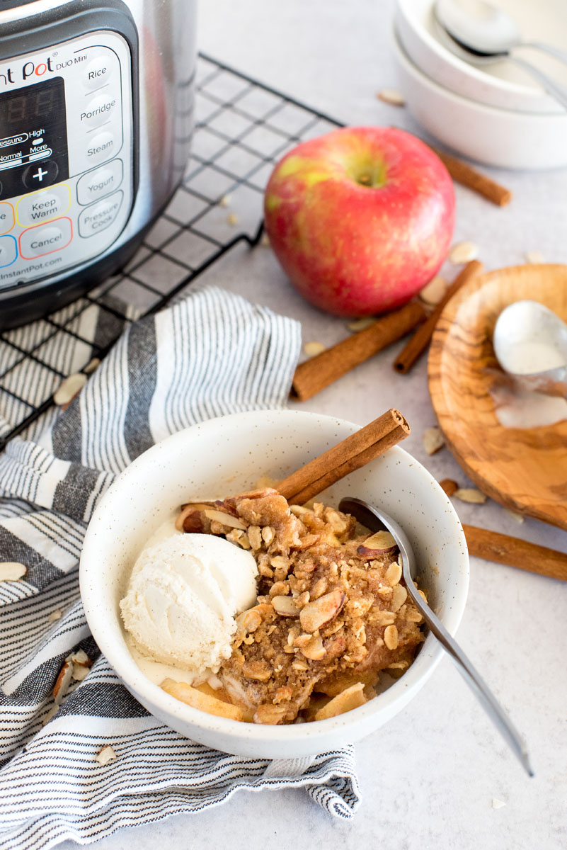 a 45 degree shot of Instant Pot apple crisp in a white bowl, with a scoop of vanilla ice cream on top, with an Instant Pot, an apple, and cinnamon sticks in the background