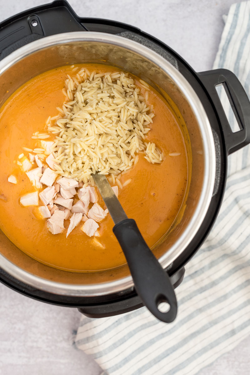 an overhead shot of the orzo pasta and the diced chicken being added to the soup
