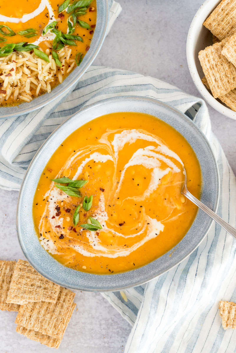 close-up of the butternut squash soup in an egg-shaped bowl, with a swirl of cream and the chicken and pasta mixed in with a larger bowl of soup in the background