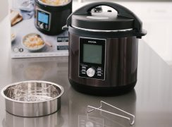 The Zavor LUX pressure cooker placed on a counter with the included trivet and steamer basket placed in front of the packaging box.