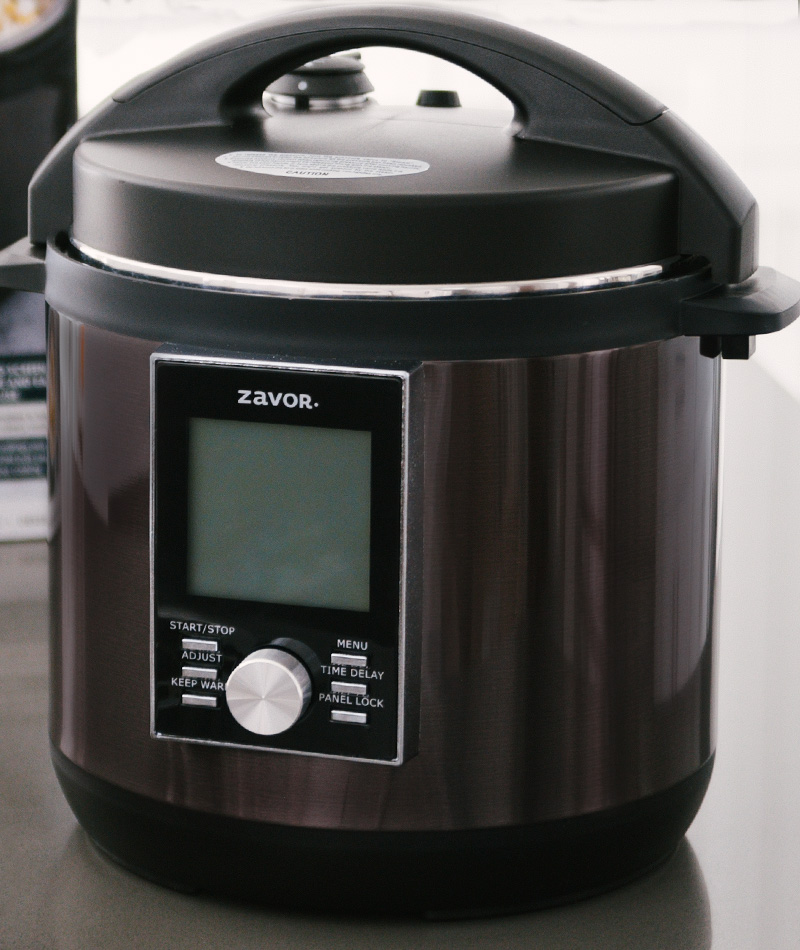 The black stainless steel Zavor Lux with an LCD screen placed on a kitchen counter.
