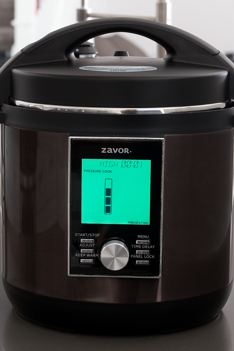 The Zavor LUX pressure cooker with the LCD screen showing the status for coming to pressure.