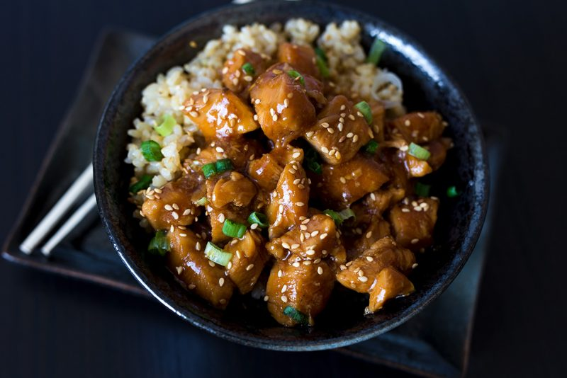 A horizontal close-up of Honey Sesame Chicken in a dark black bowl against a dark black background, with chopsticks tucked under the bowl