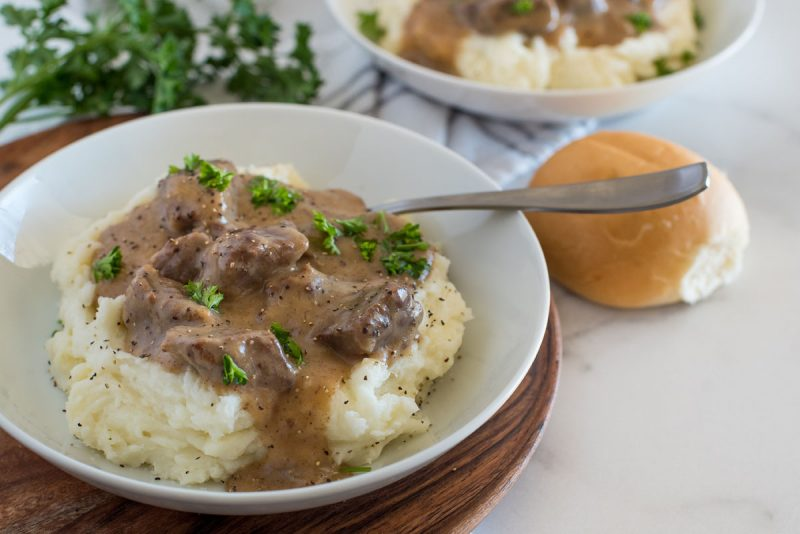 white bowl with swedish kalops beef stew over mashed potatoes