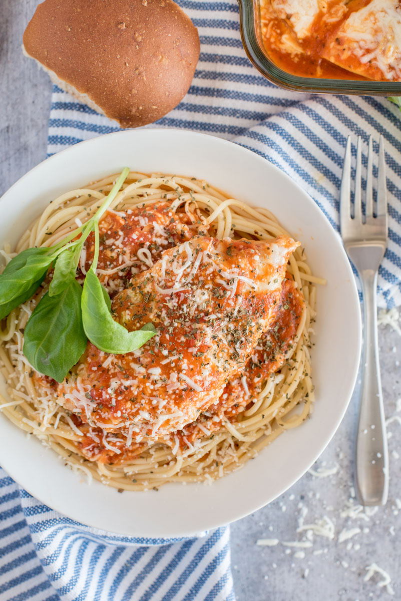 Overhead shot of chicken marinara that was cooked in a pressure cooker, that is served over spaghetti and garnished with fresh basil.