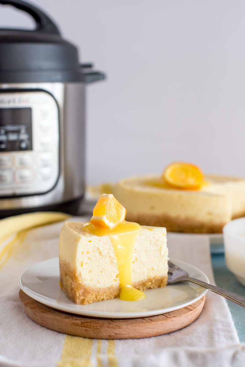 instant pot with a slice of lemon cheesecake in front on a plate
