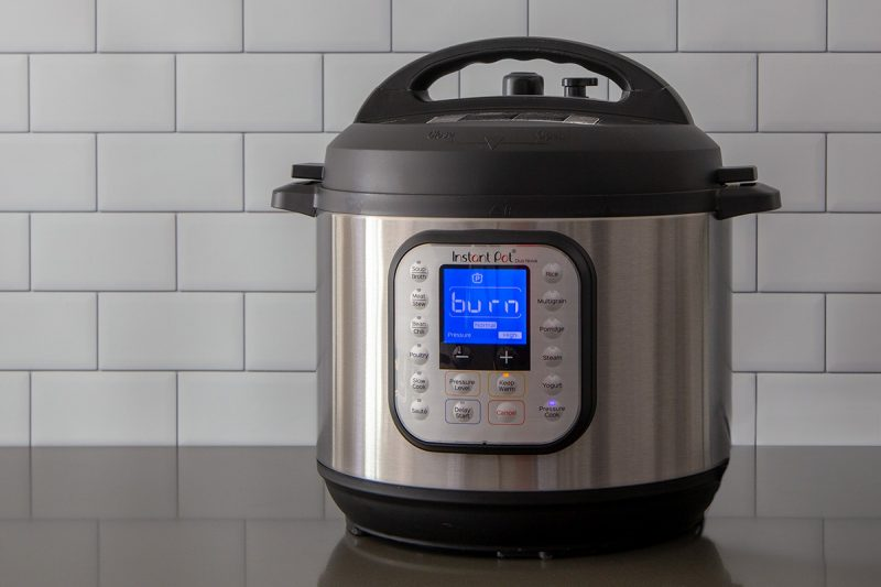 An Instant Pot Duo Nova on a gray counter displaying the burn notice on a blue digital screen