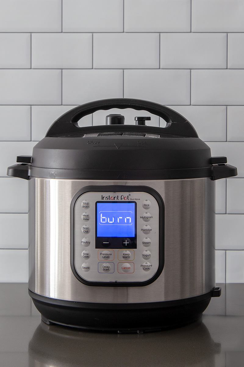 A tight, head-on vertical shot of an Instant Pot Duo Nova on a gray counter displaying the burn warning on a blue digital screen