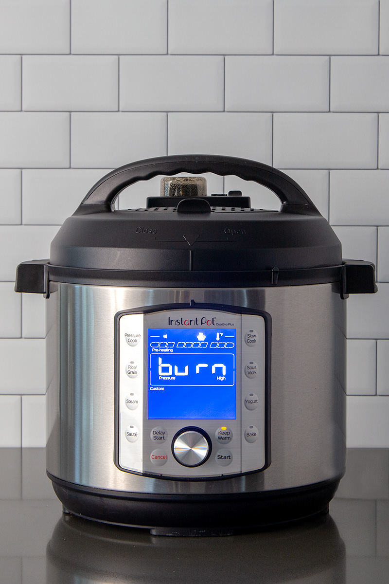 A tight vertical shot of an Instant Pot Duo Evo Plus showing a burn message on a gray counter and a white subway tile background