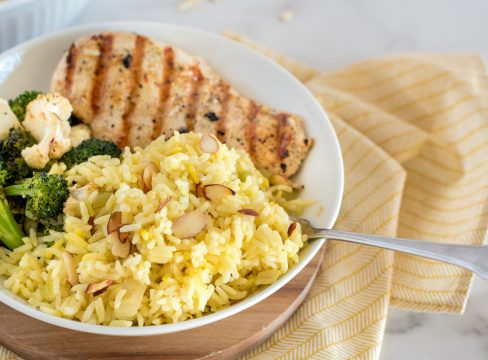 saffron rice pilaf with grilled chicken in a white bowl