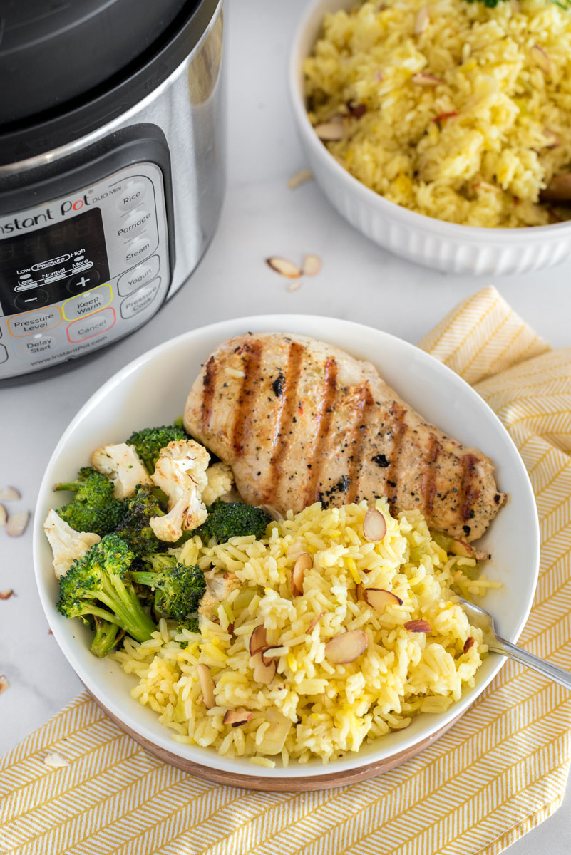 bowl of saffron almond irce pilaf with grilled chicken breast and broccoli