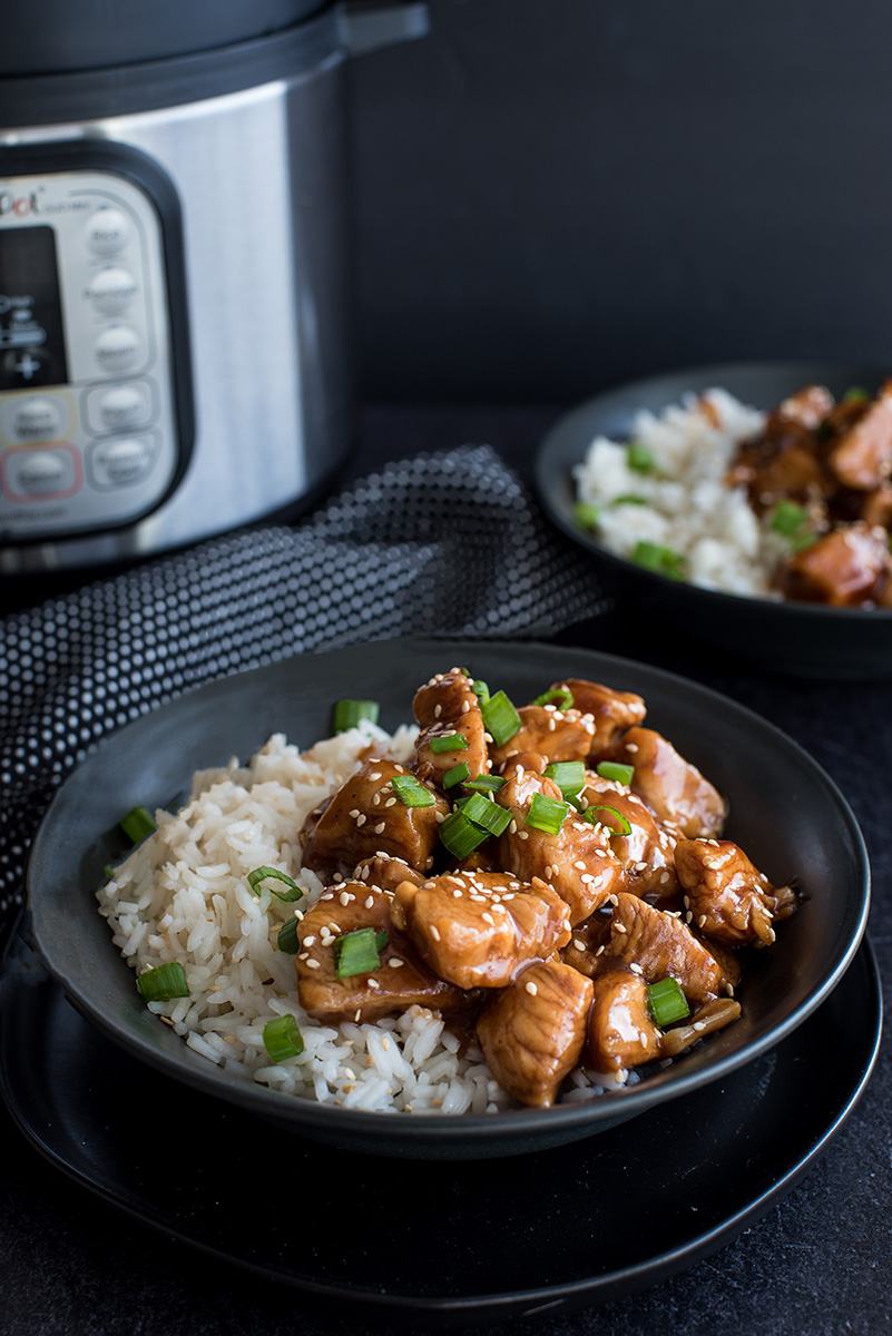 Close up on a black bowl filled with Instant Pot fluffy white rice and pressure cooker Honey Sesame Chicken garnished with sliced fresh scallions, white sesame seeds and sticky soy honey sauce with an Instant Pot in the background.