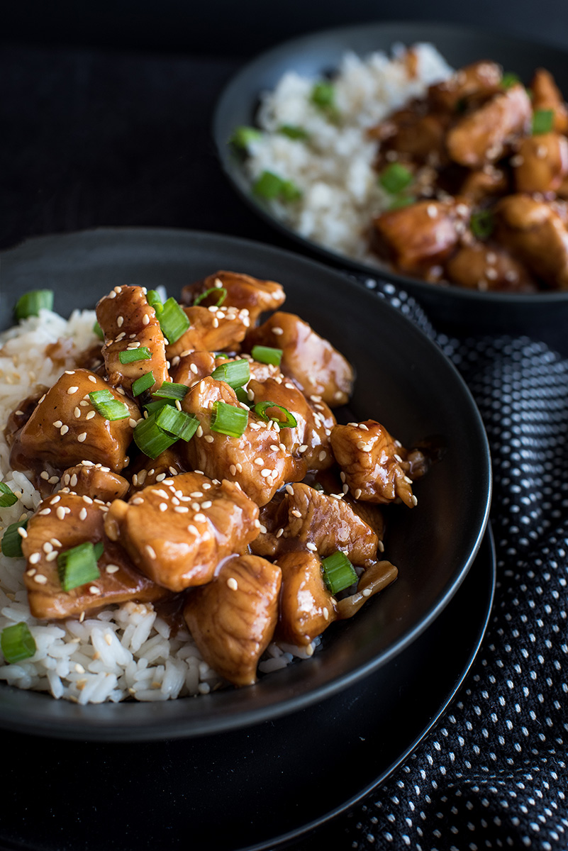 Close up on two bowls filled with Pressure Cooker white rice and Instant Pot Honey Sesame Chicken garnished with freshly cut green onions, white sesame seeds, and a sticky honey soy sauce.