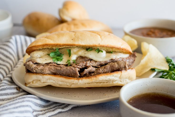 A close up of an Instant Pot French dip sandwich topped with cheese on a bun next to a bowl of au jus.