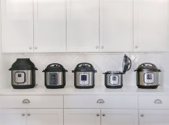 Five different models of Instant Pot on a white counter with white cabinets and a white tile backsplash in the background