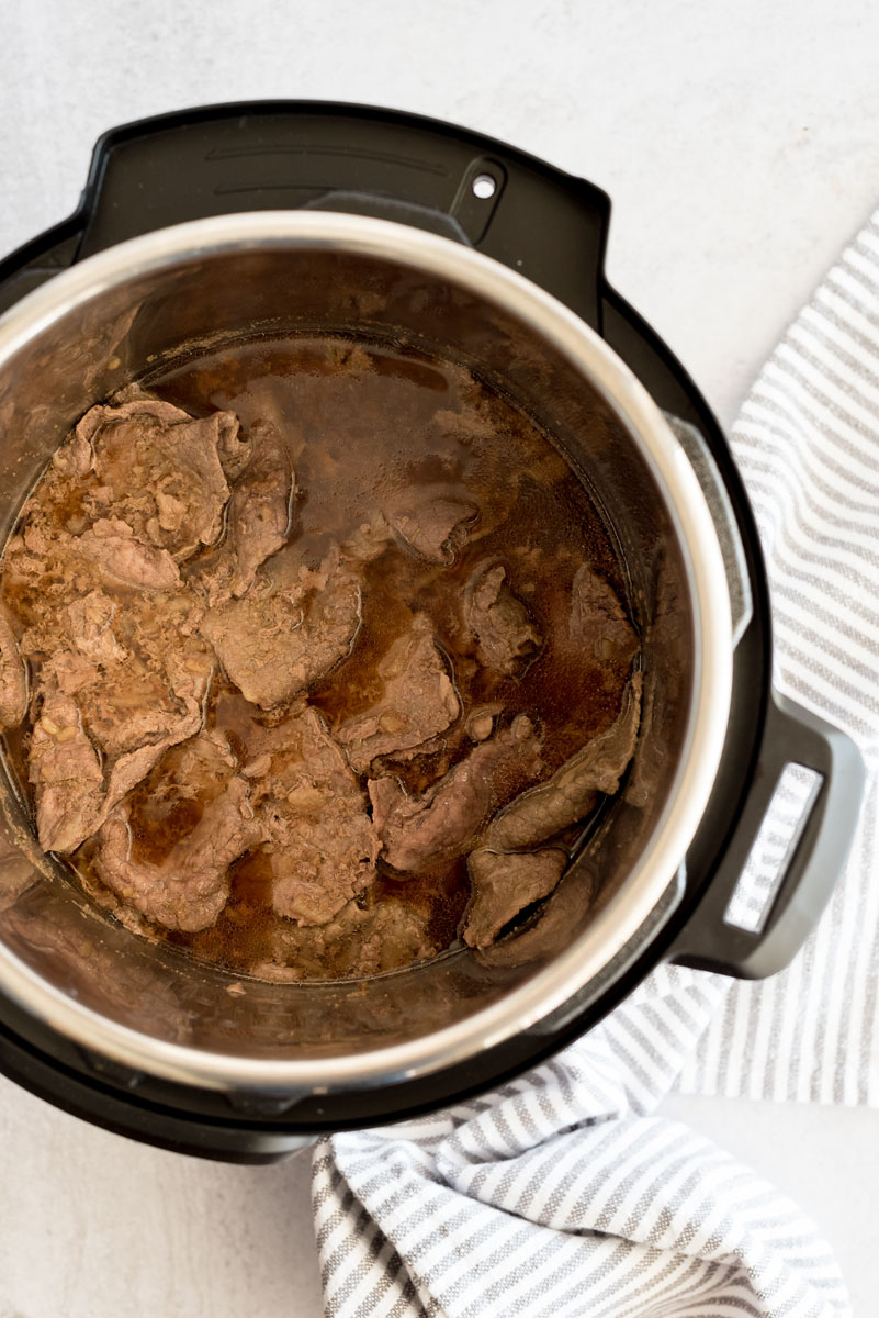 Overhead shot of sliced beef cooked in au jus inside an Instant Pot.