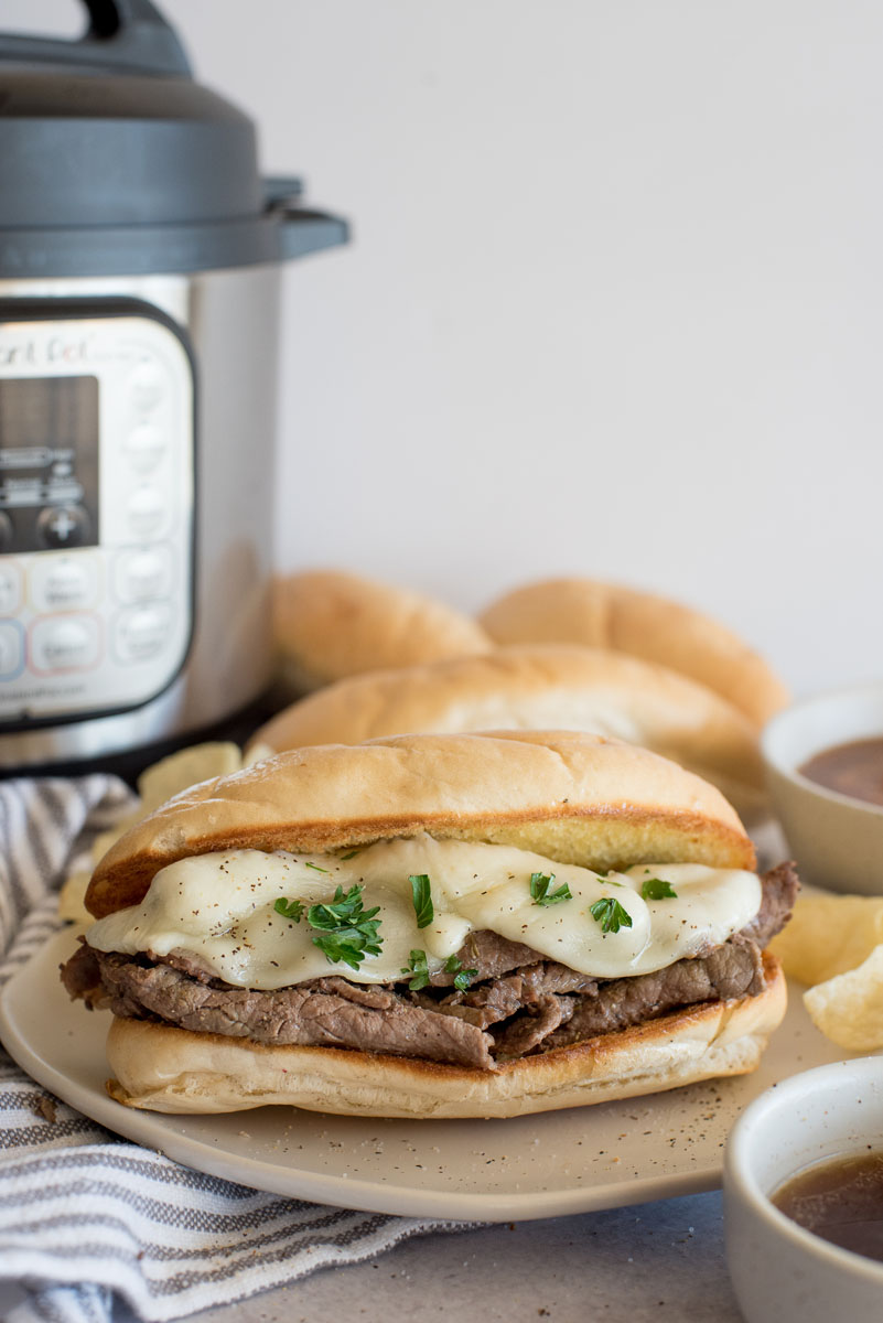 A French dip sandwich topped with cheese on a bun and placed in front of an Instant Pot.